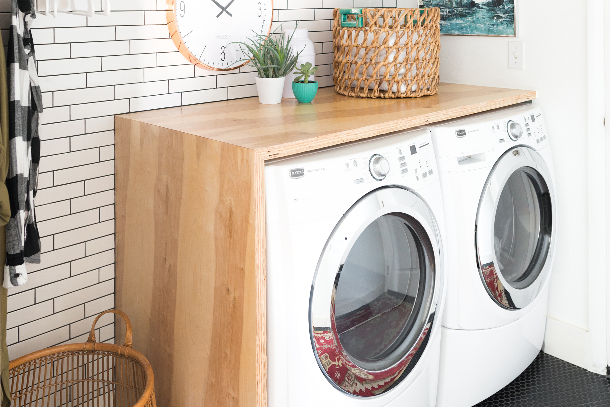 Laundry room with white subway tile and black tiled floor