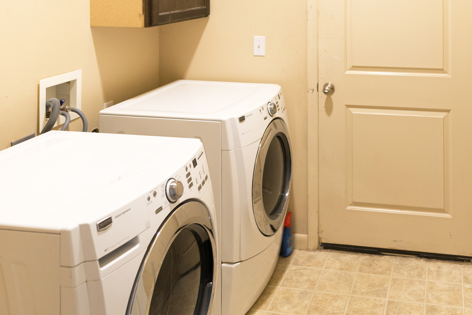 Beige laundry room with outdated beige tile