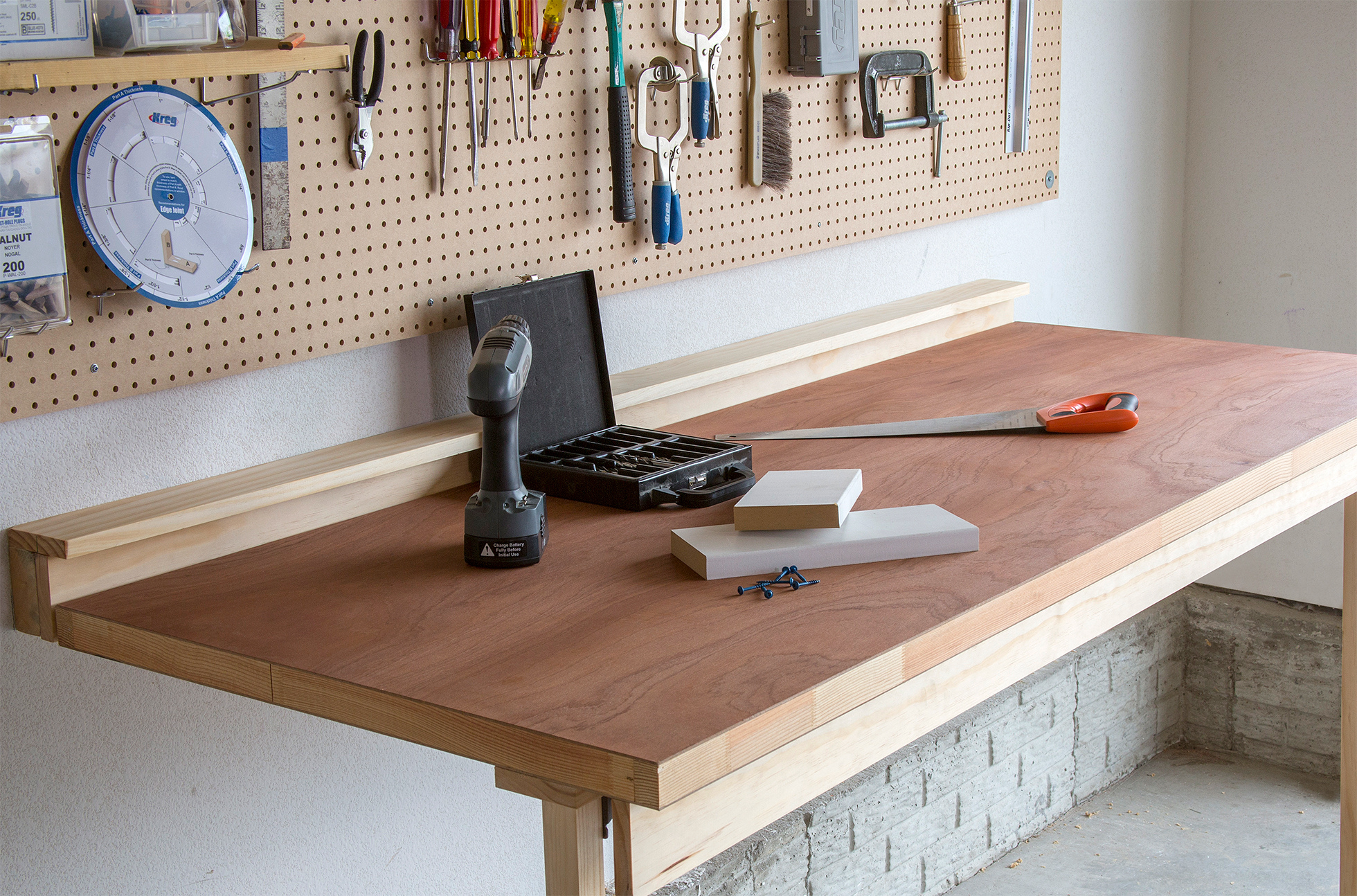 A wood workbench with tools in a garage