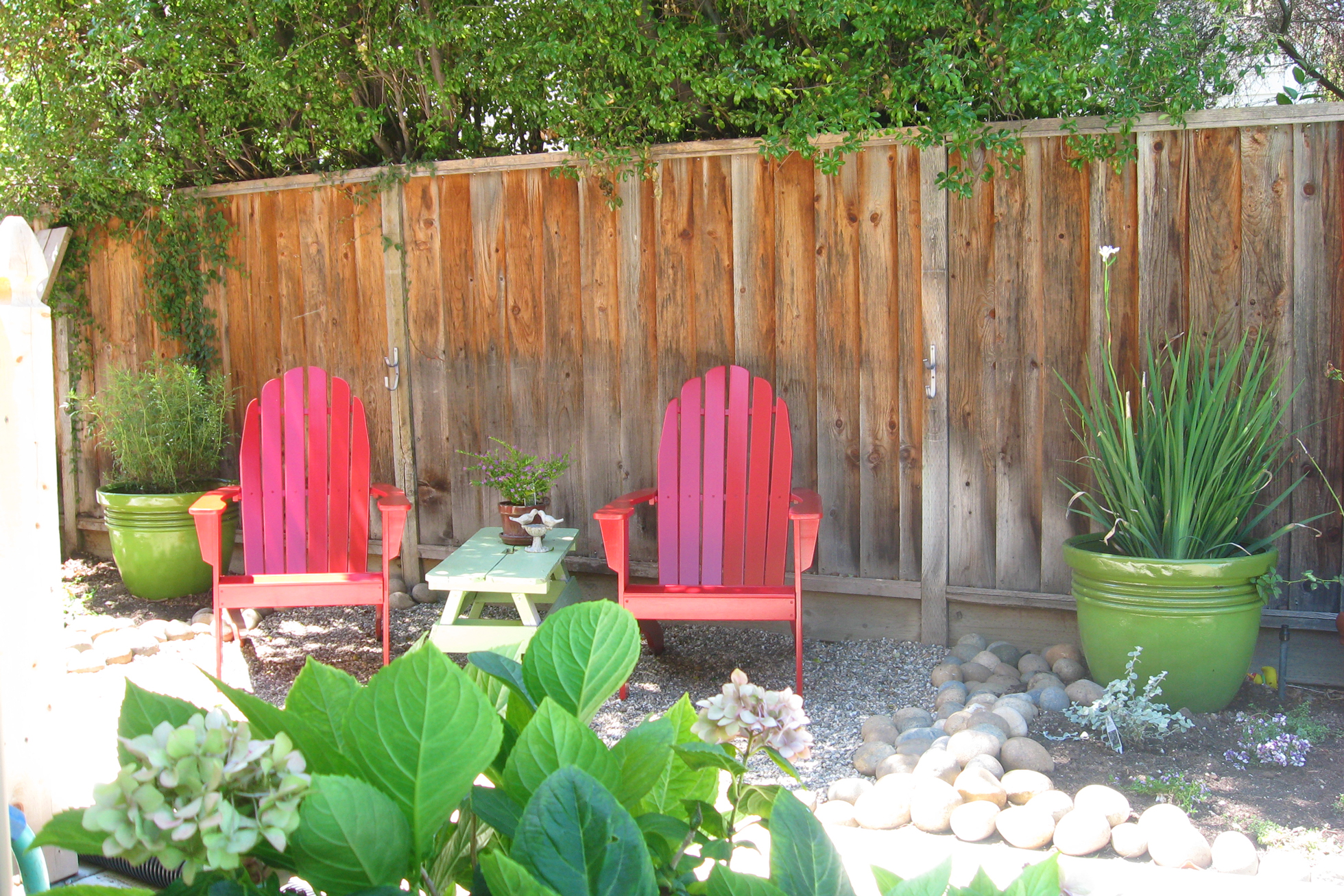Red Adirondack chairs in a gravel backyard