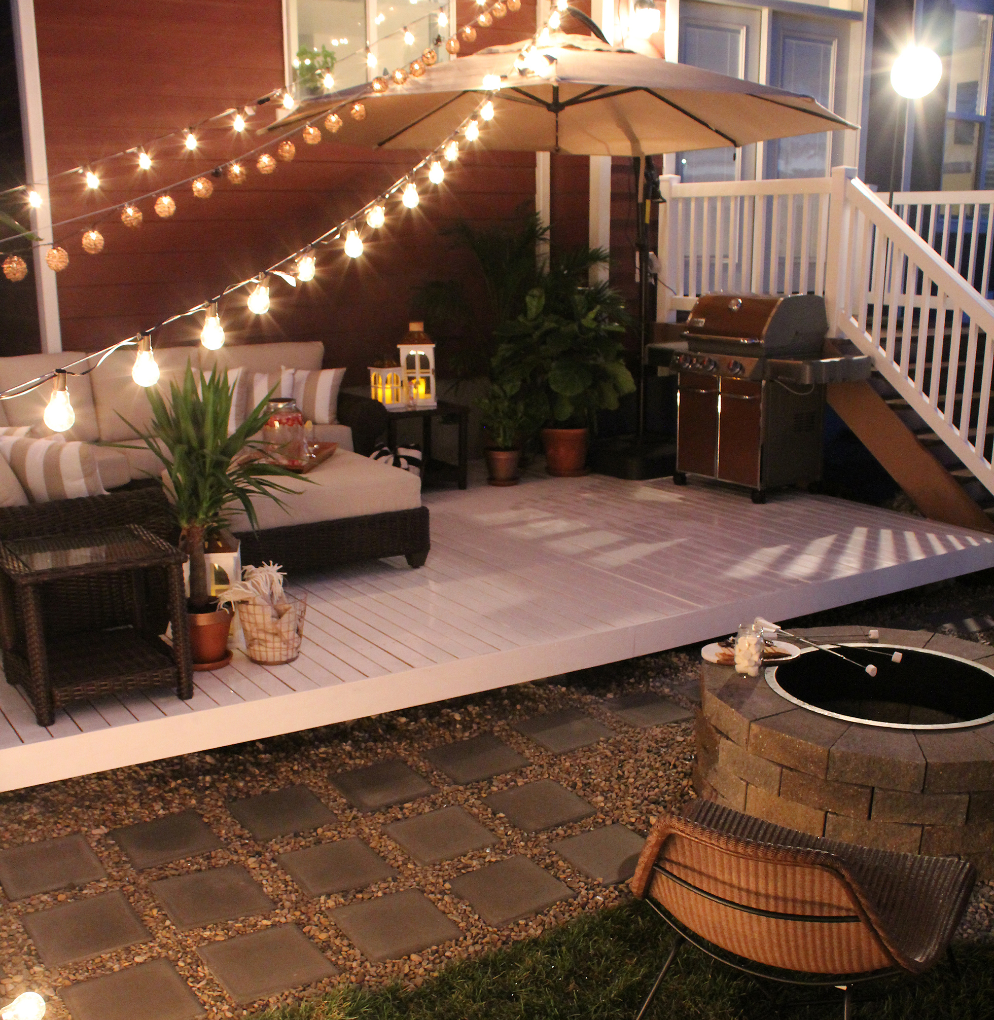 A light-colored deck with patio furniture at night