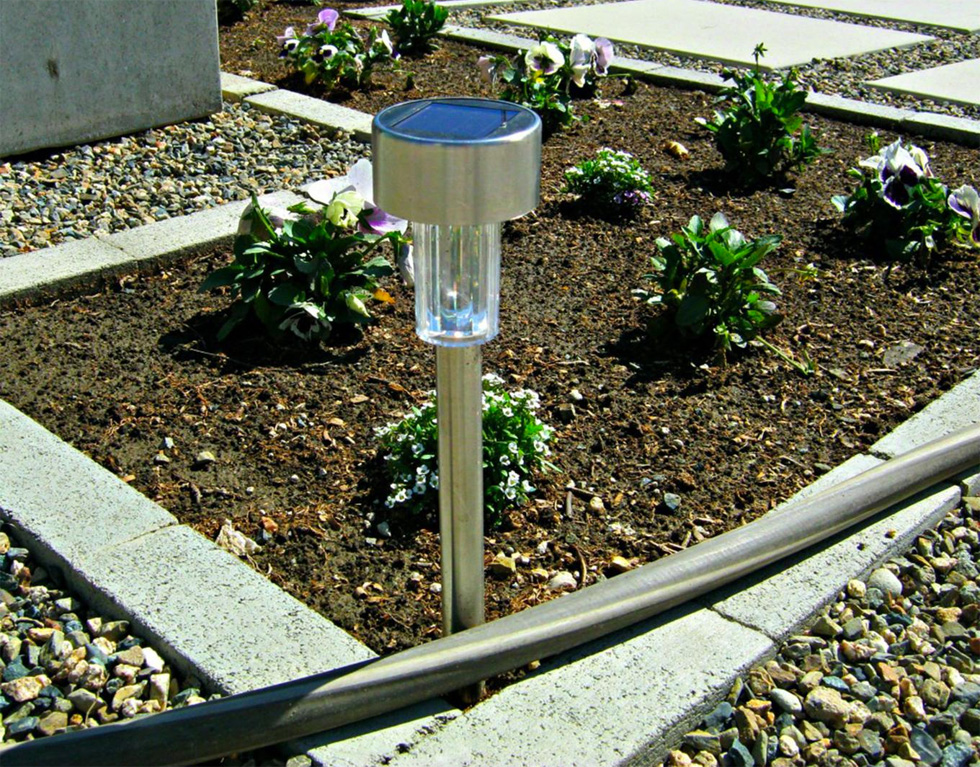 A solar light stands in dirt