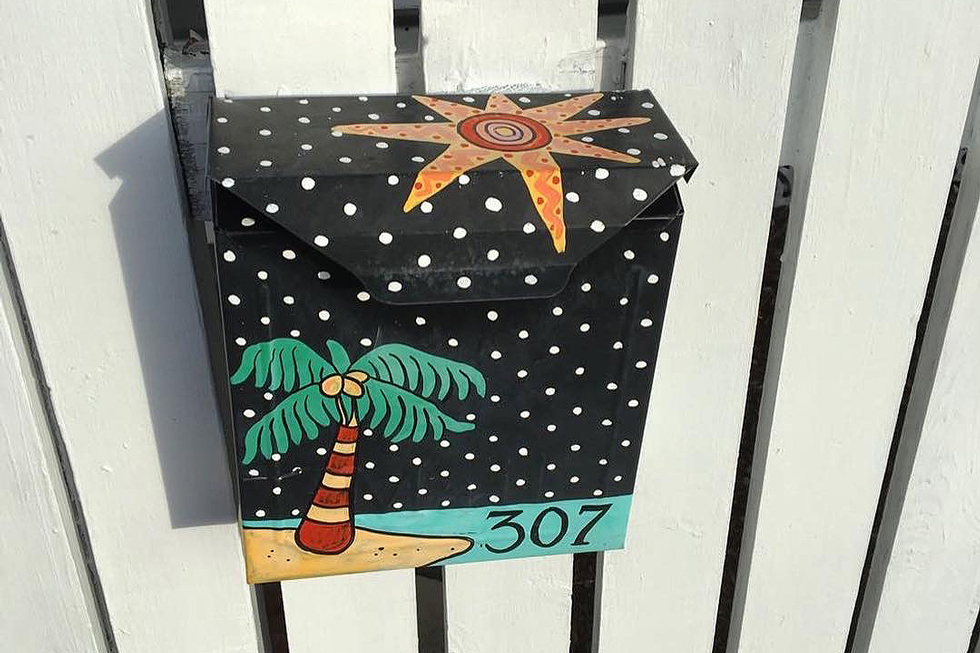 A black mailbox with a palm tree and beach illustration