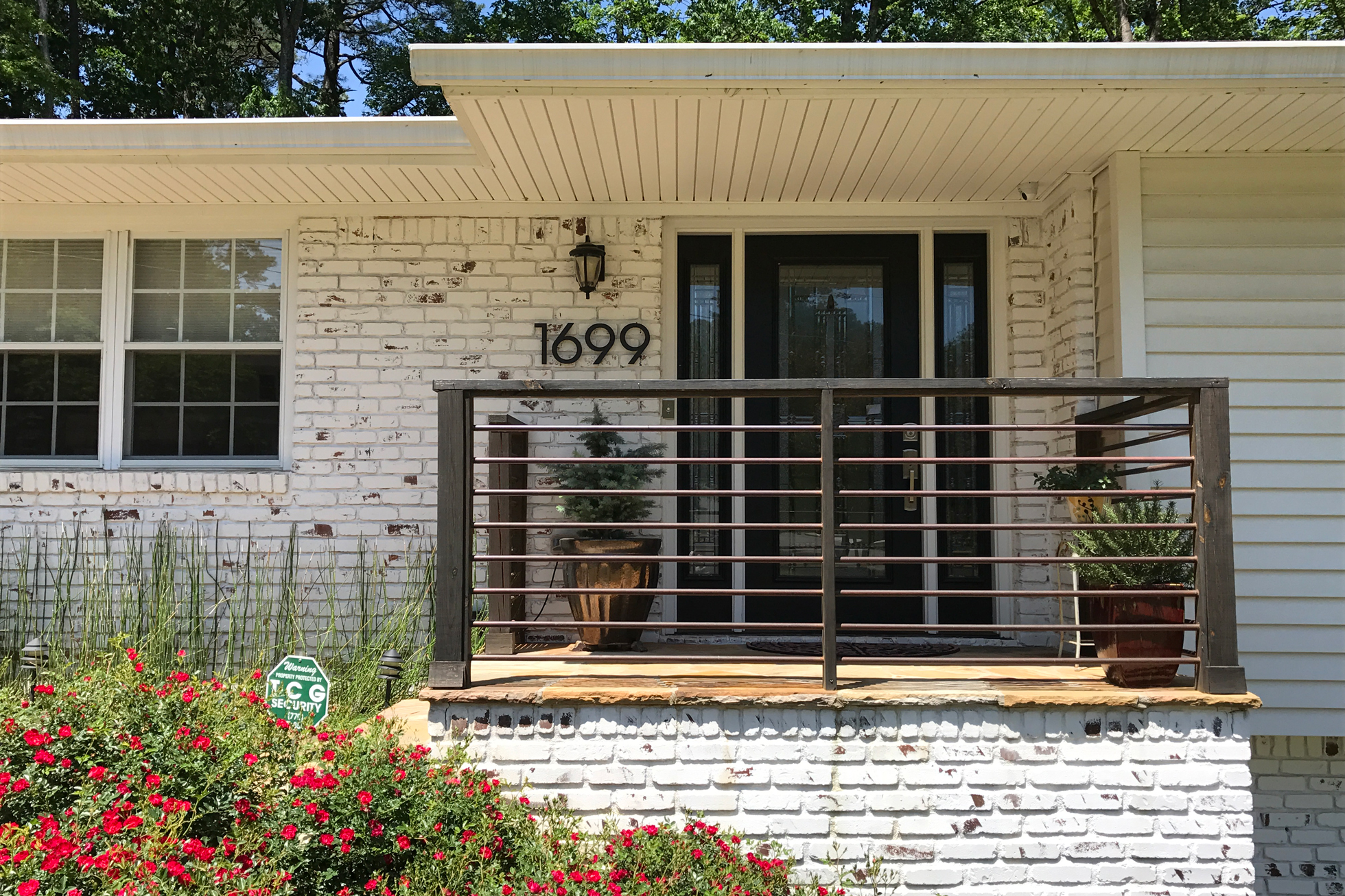 A white brick home with front porch and metal home numbers