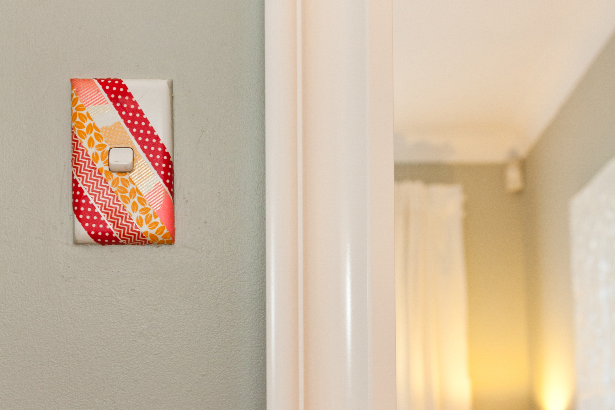 A pink and orange covered light switch on a cream wall