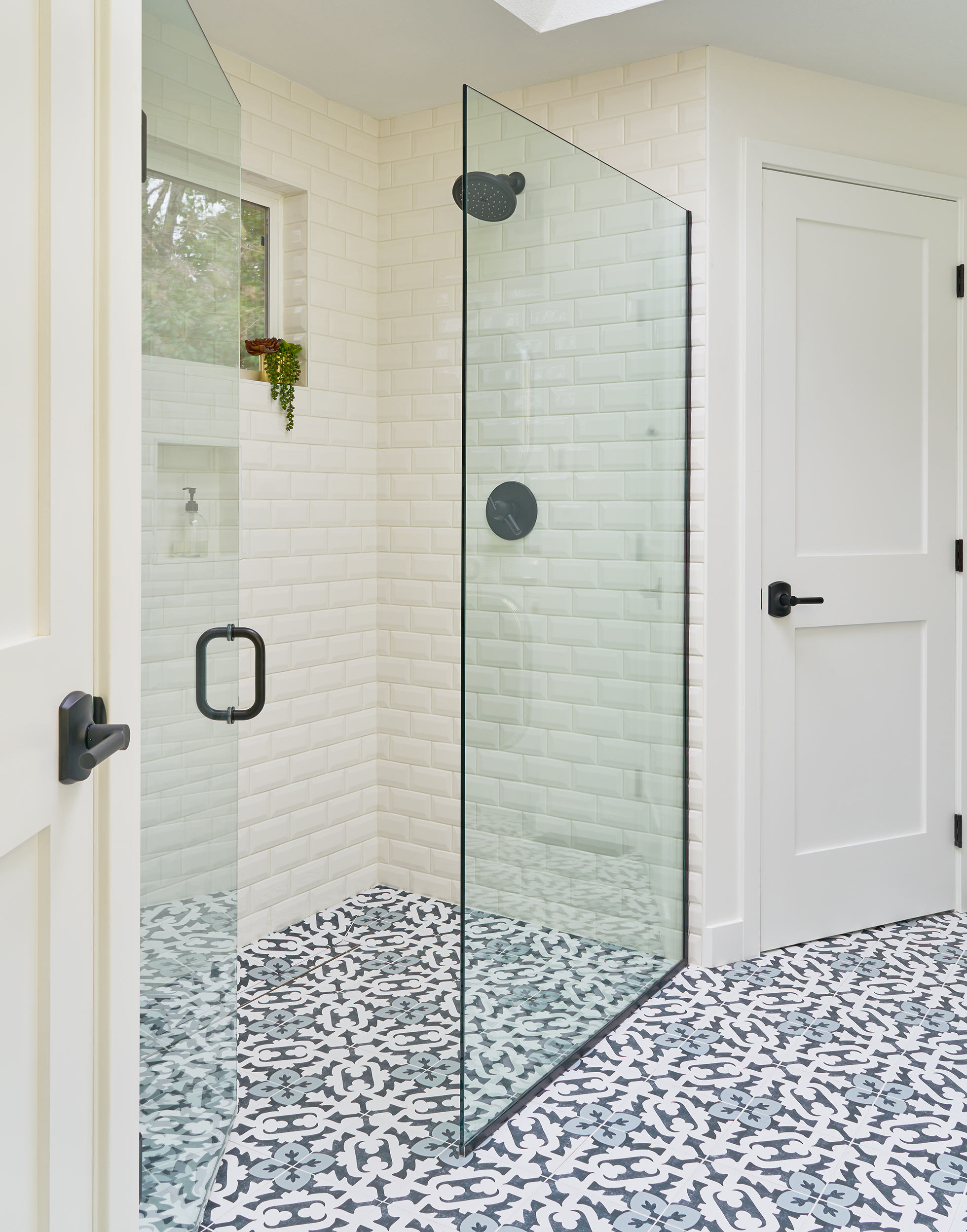 Salle de bain carrelée avec douche sans bordure et poignées de porte à levier