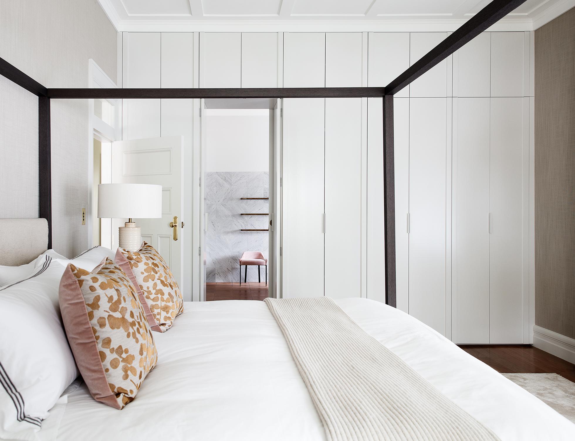 Chambre blanche avec lit à baldaquin blanc et oreillers roses