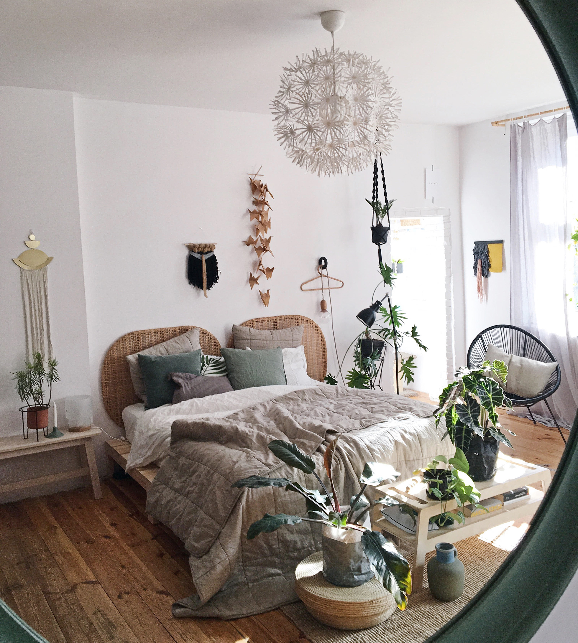 View of boho bedroom with southern exposure in mirror