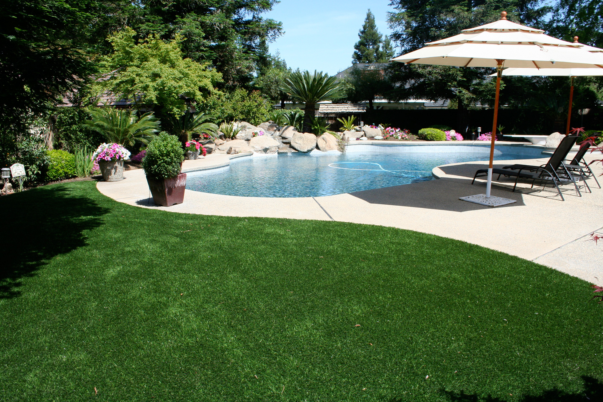 Synthetic lawn around a back yard pool | Fake grass