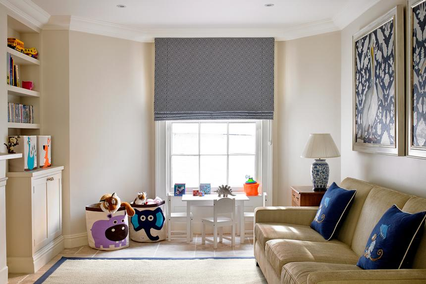 A living room with couch and blue roman shades on window