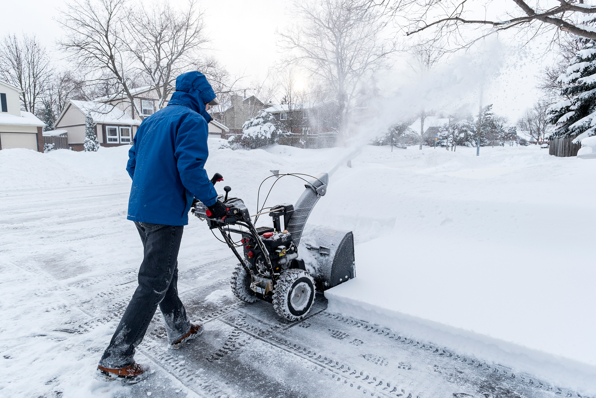 A man in a blue coat using a snow blower in a neighborhood