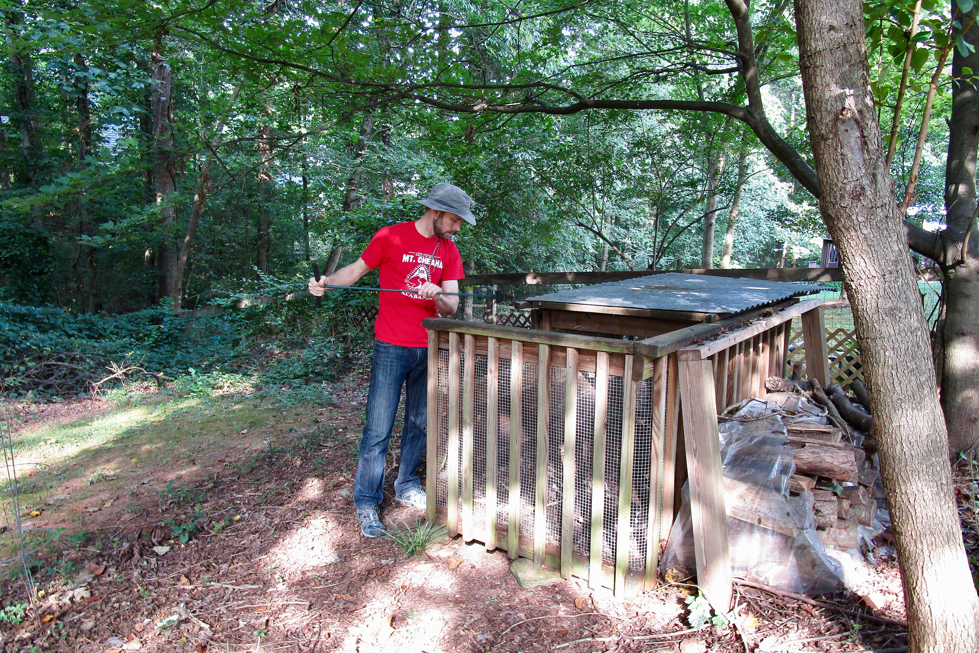 A man in a red shirt is opening a compost bin