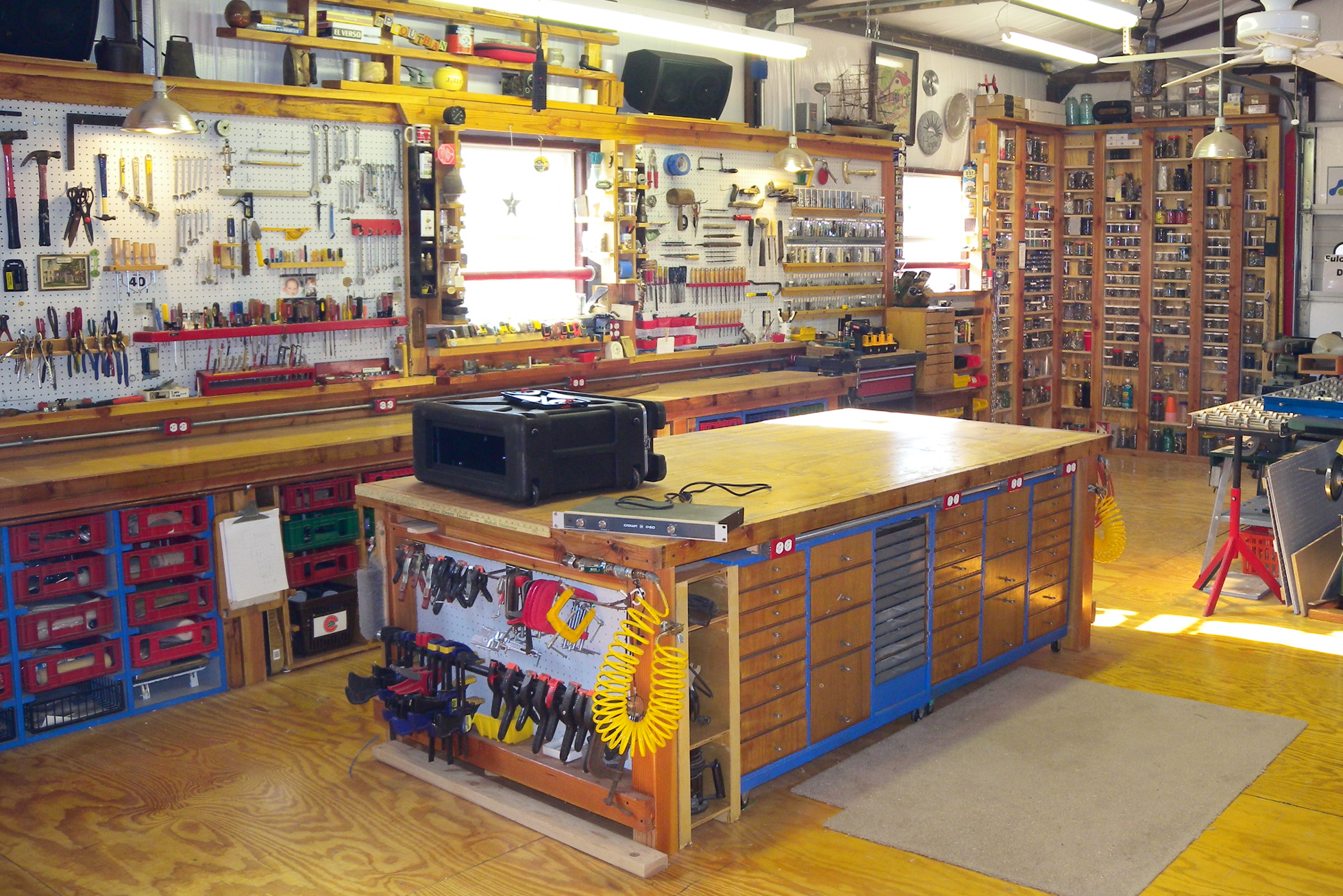 A large garage with multiple workbenches and a pegboard