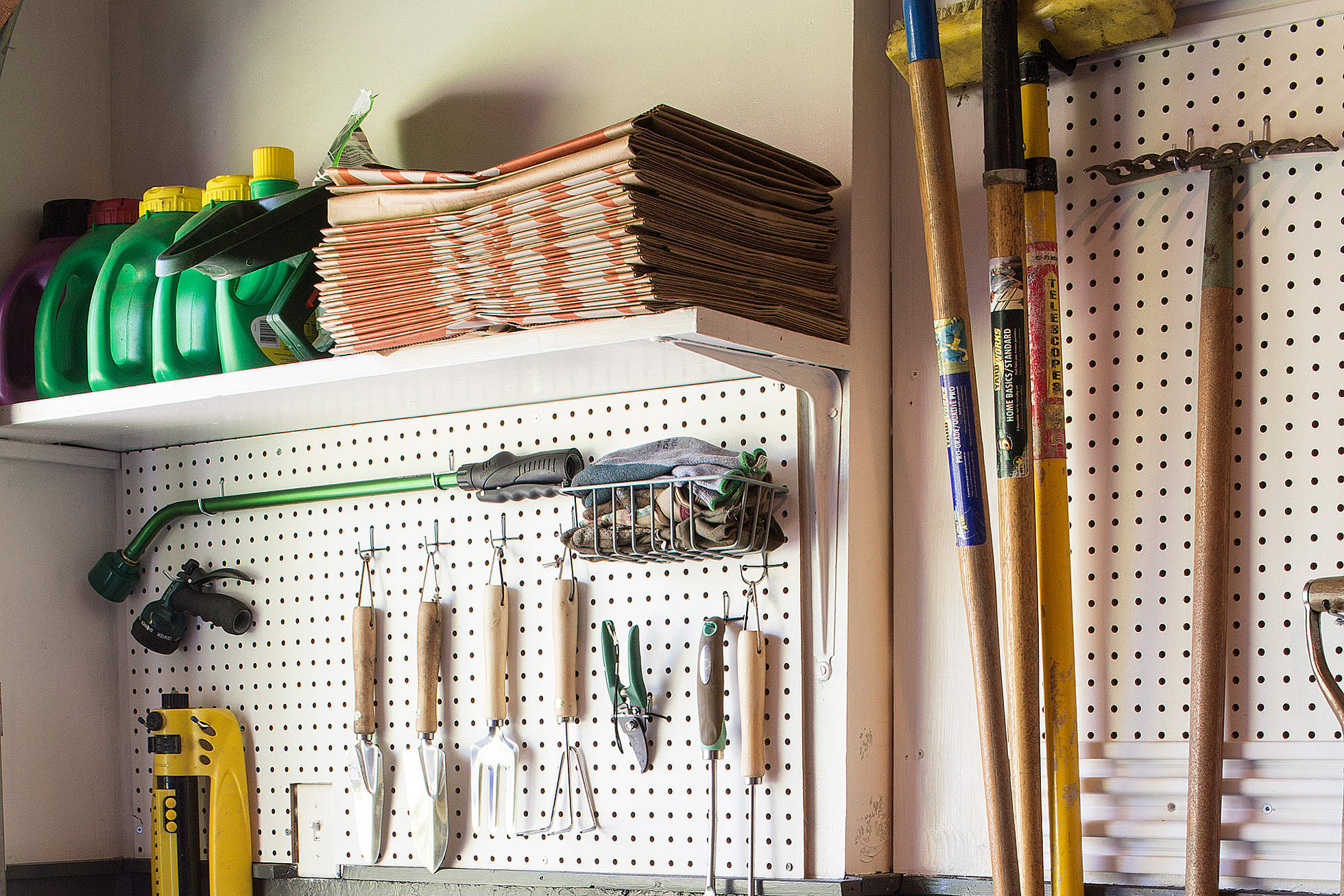 A white pegboard with hanging tools in a garage