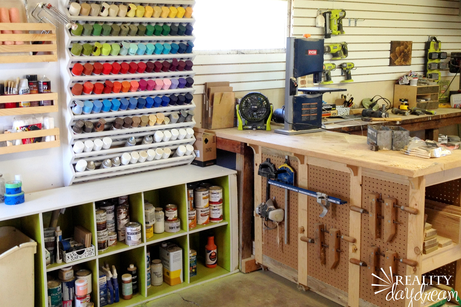 A garage with wood workbench and spray paint storage