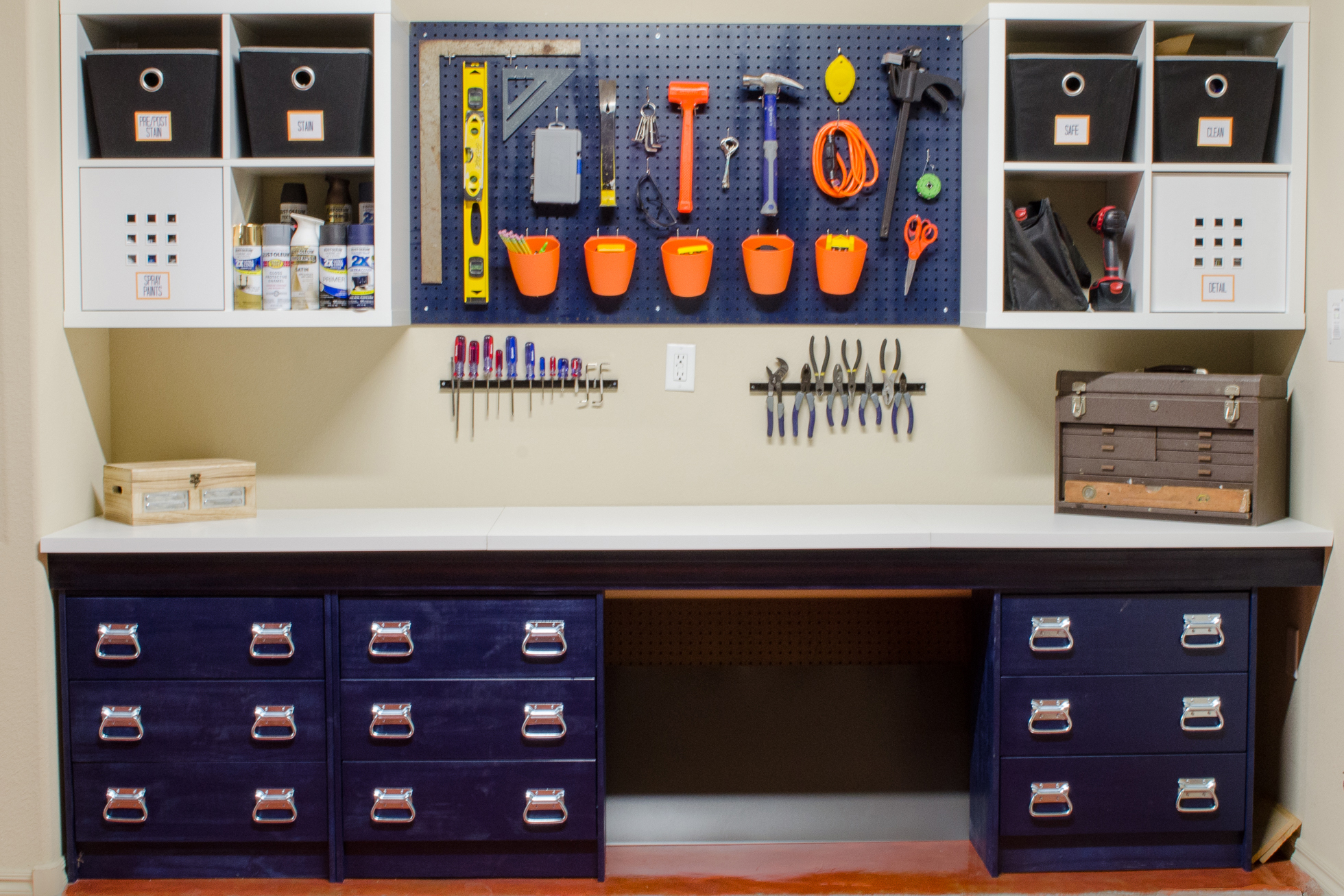 A blue workbench in a garage with a blue pegboard