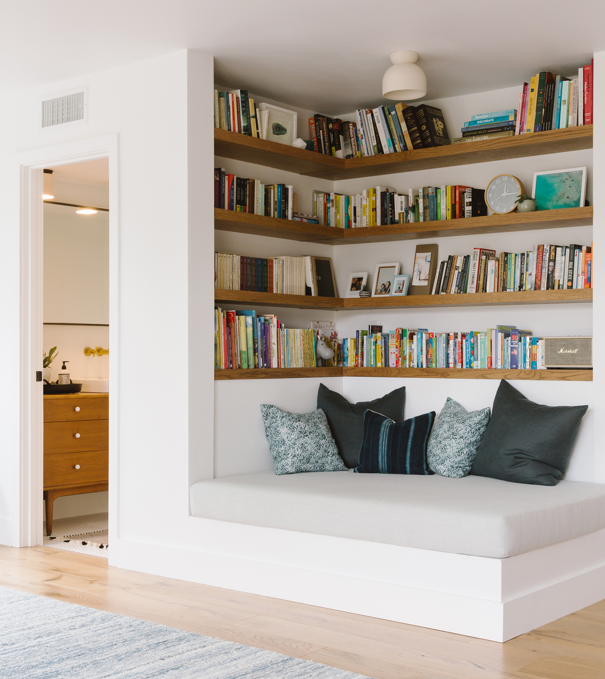 White built-in bookshelves with cushioned bench at bottom