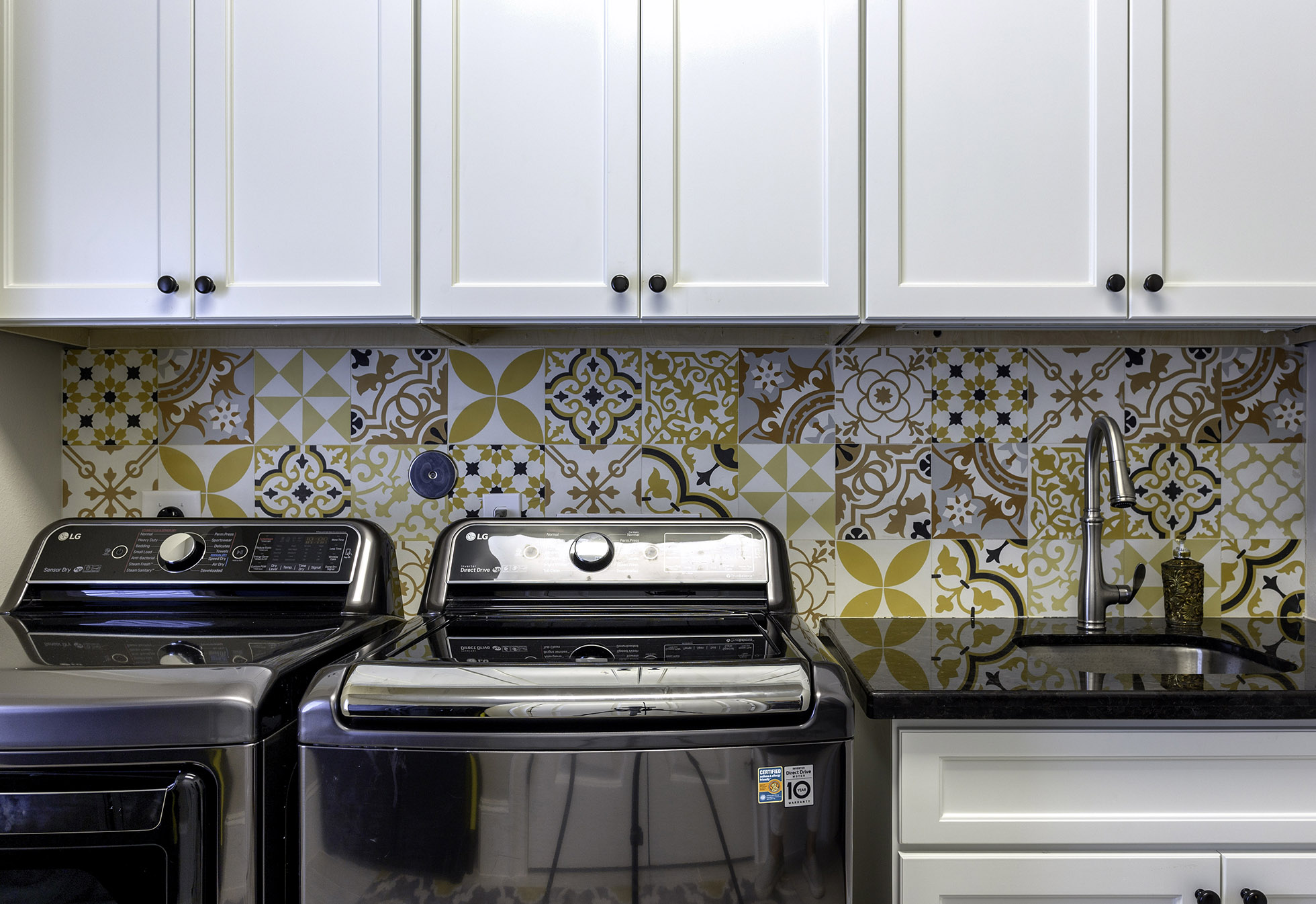 Washer and dryer side beside in front of colorful tile