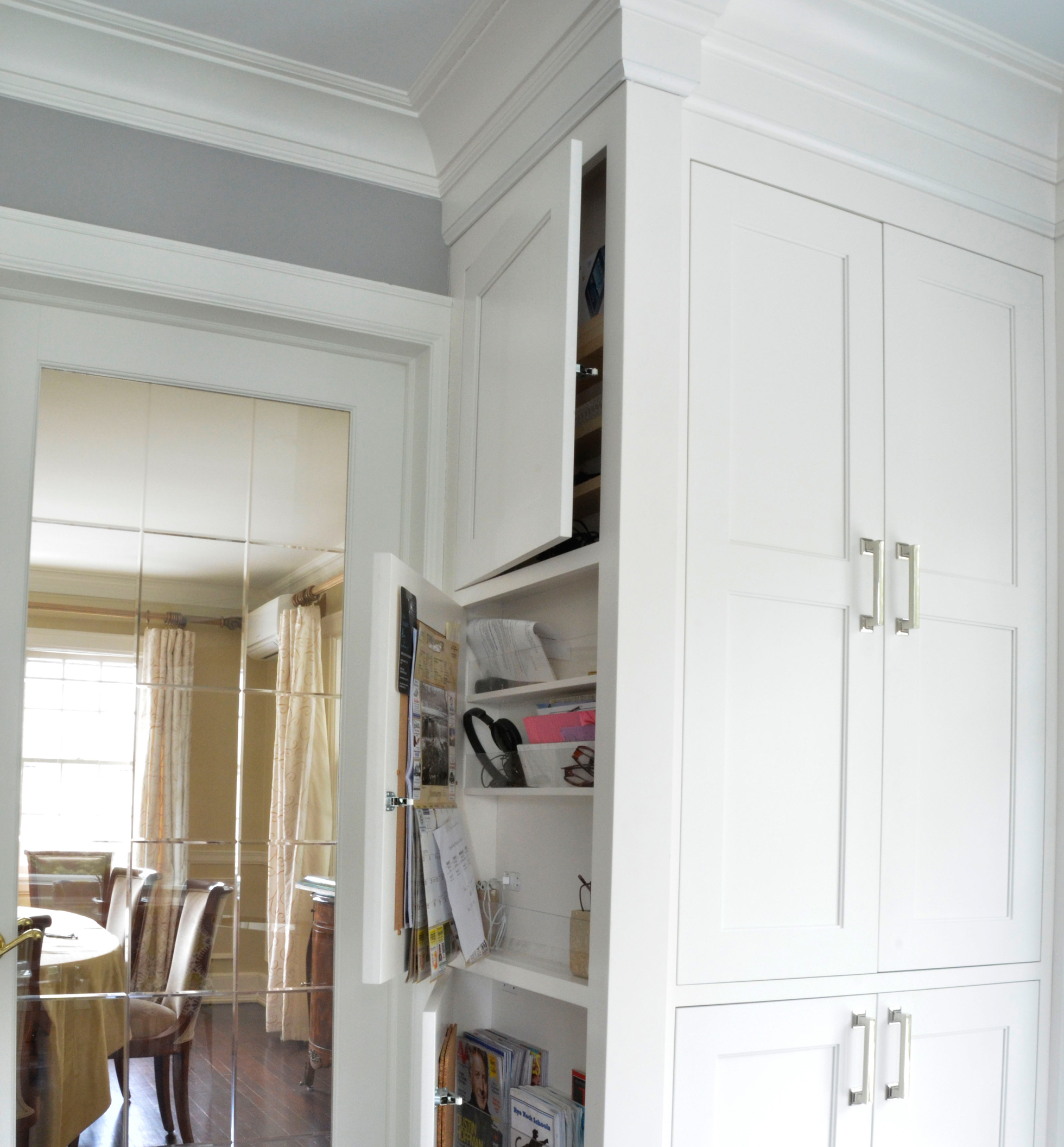 White cabinets conceal storage in a kitchen