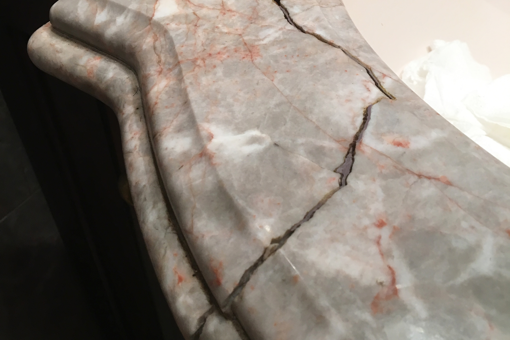 A cracked gray and pink marble stone countertop