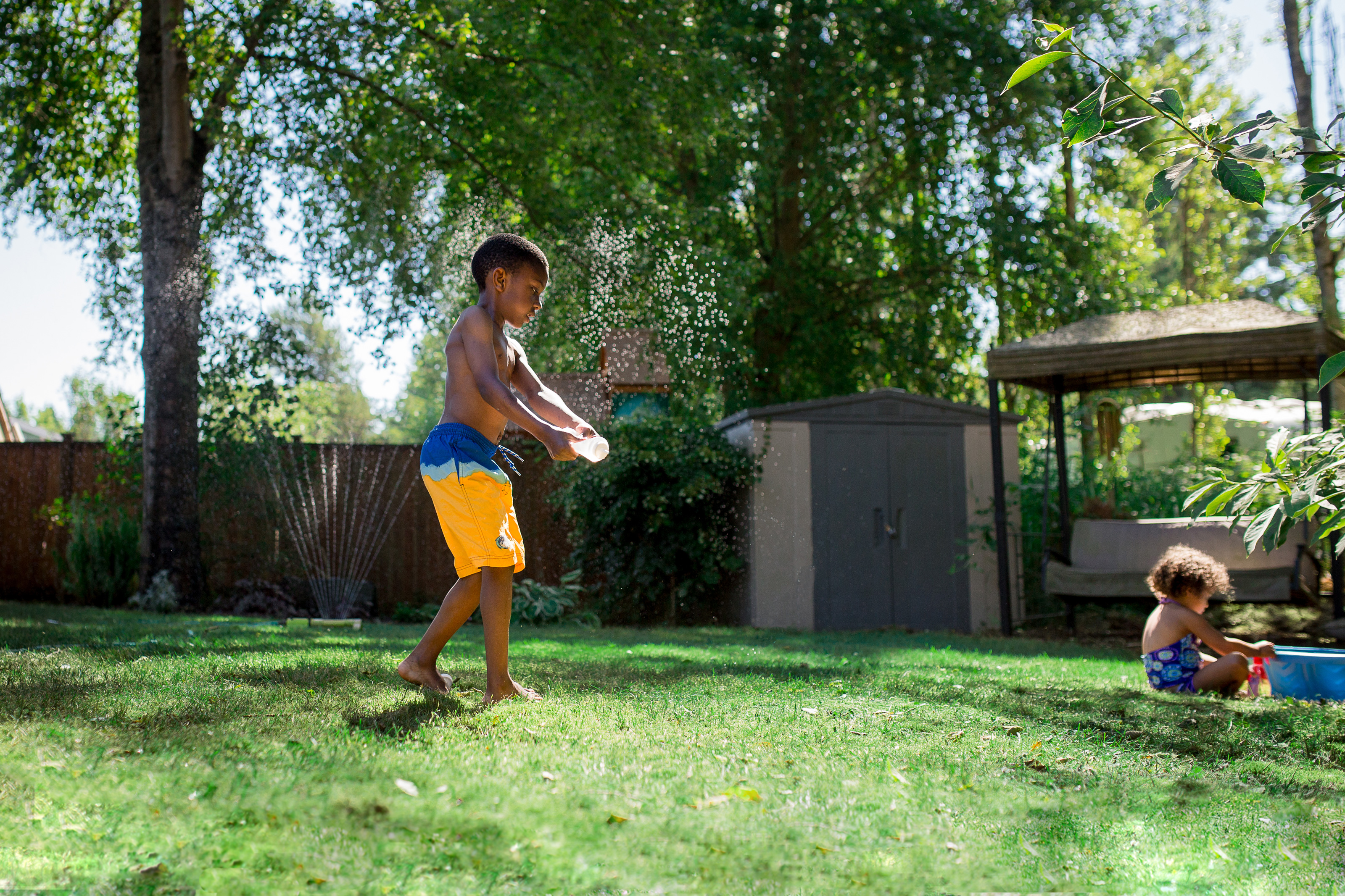 Boy playing in the lawn sprinkler at home