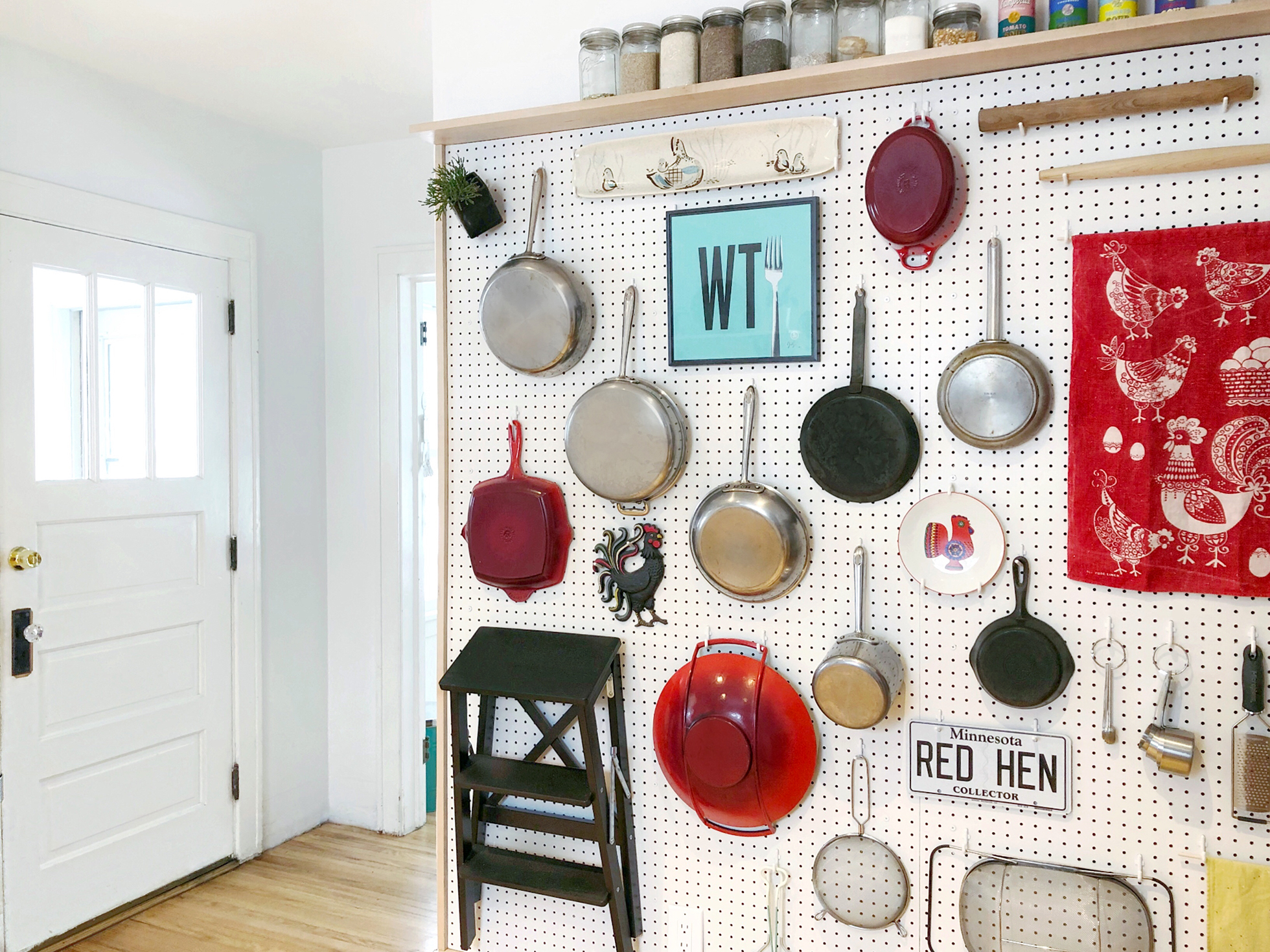 Pegboard in kitchen hanging pots, pans, and other items