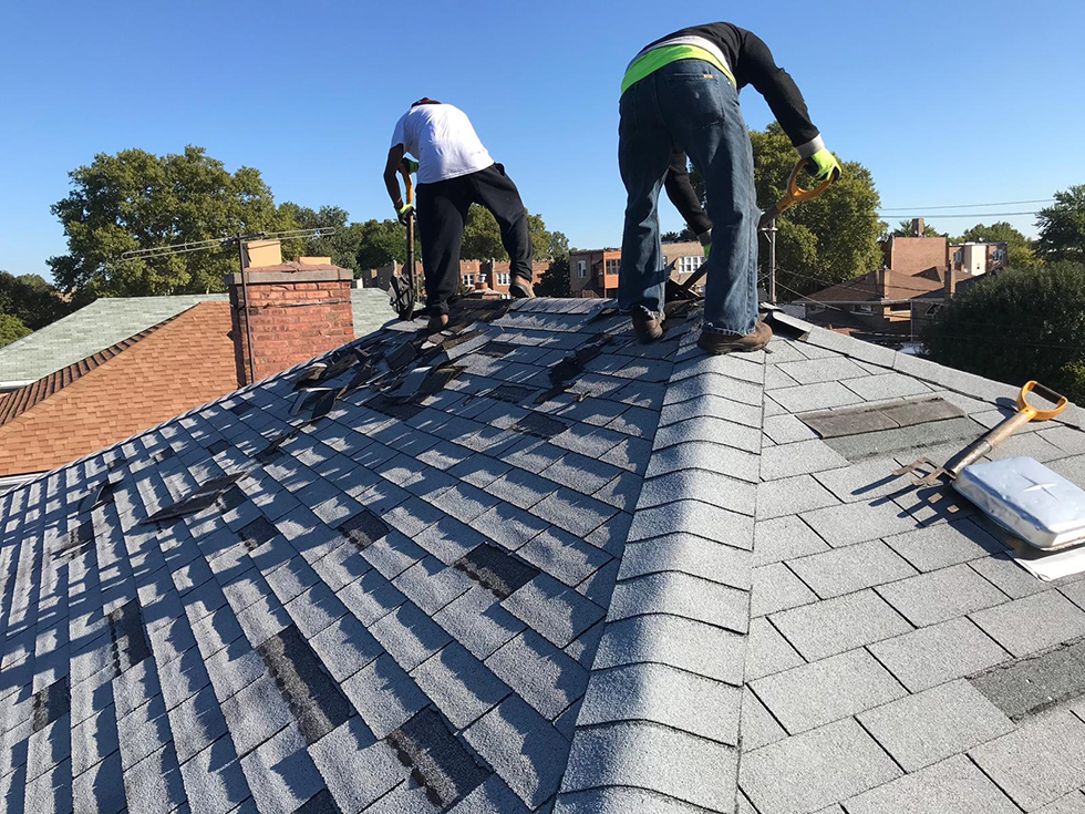 Two men work on a gray shingled roof with houses in distance