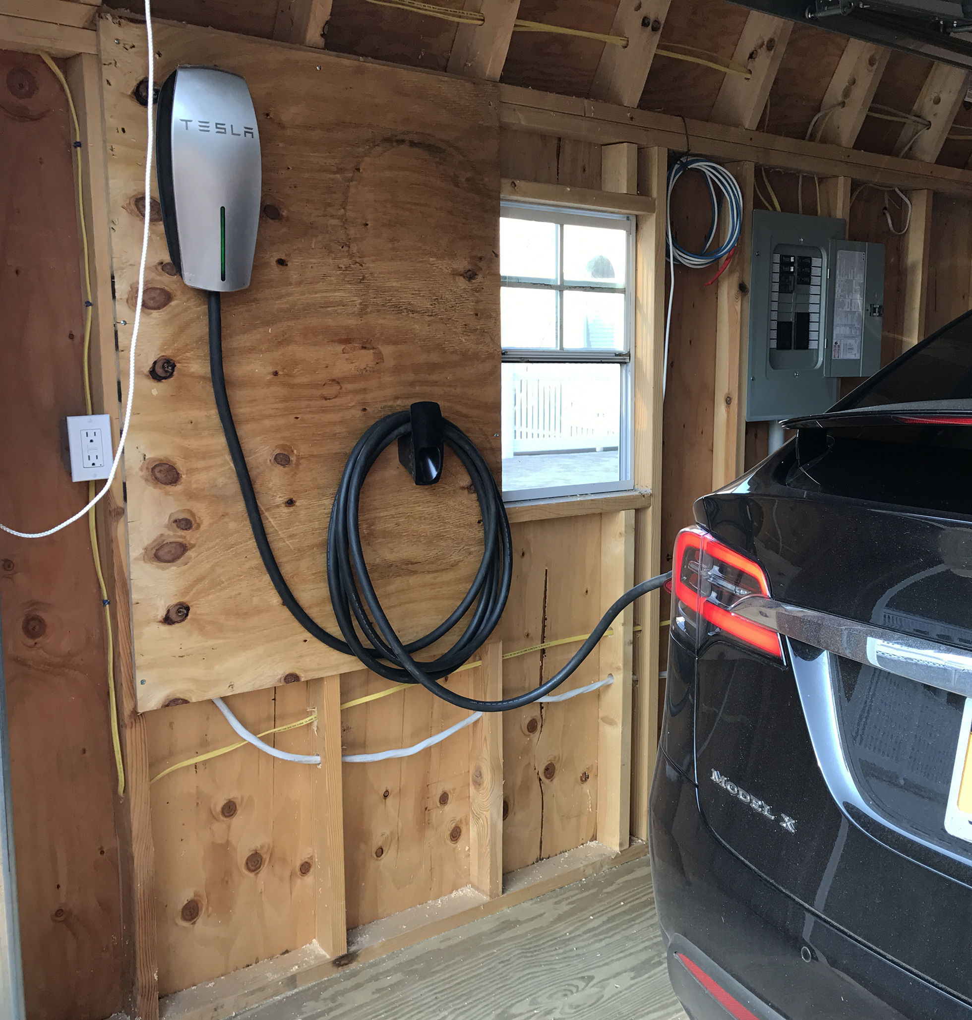 Wood-paneled garage with black electric car charging