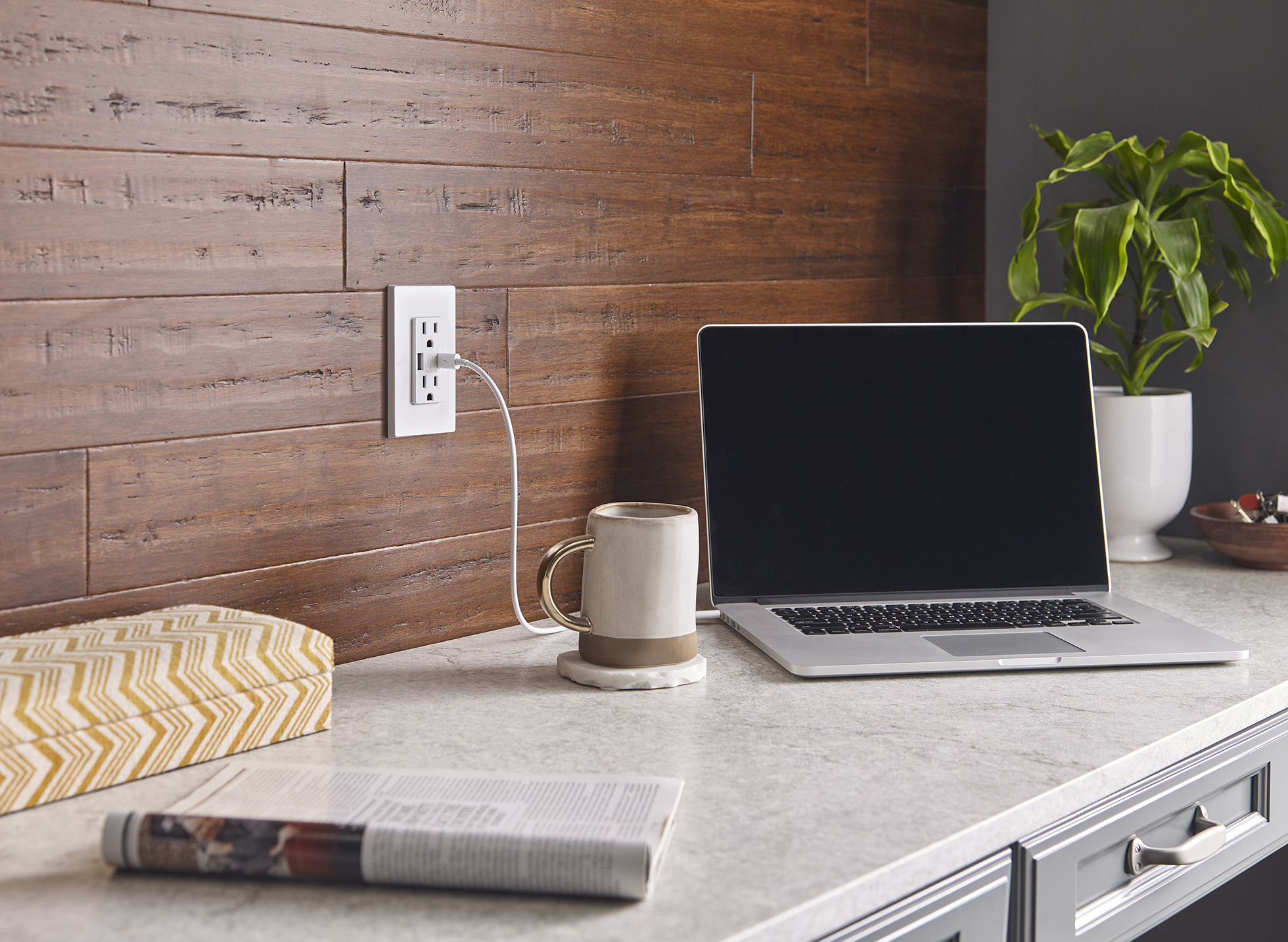 Quick charge USB port beside Mac laptop and mug on marble