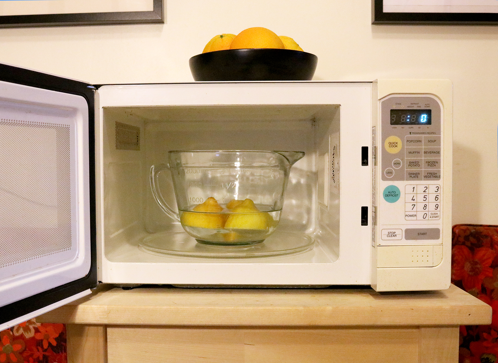 Three lemons in a bowl of water inside a microwave
