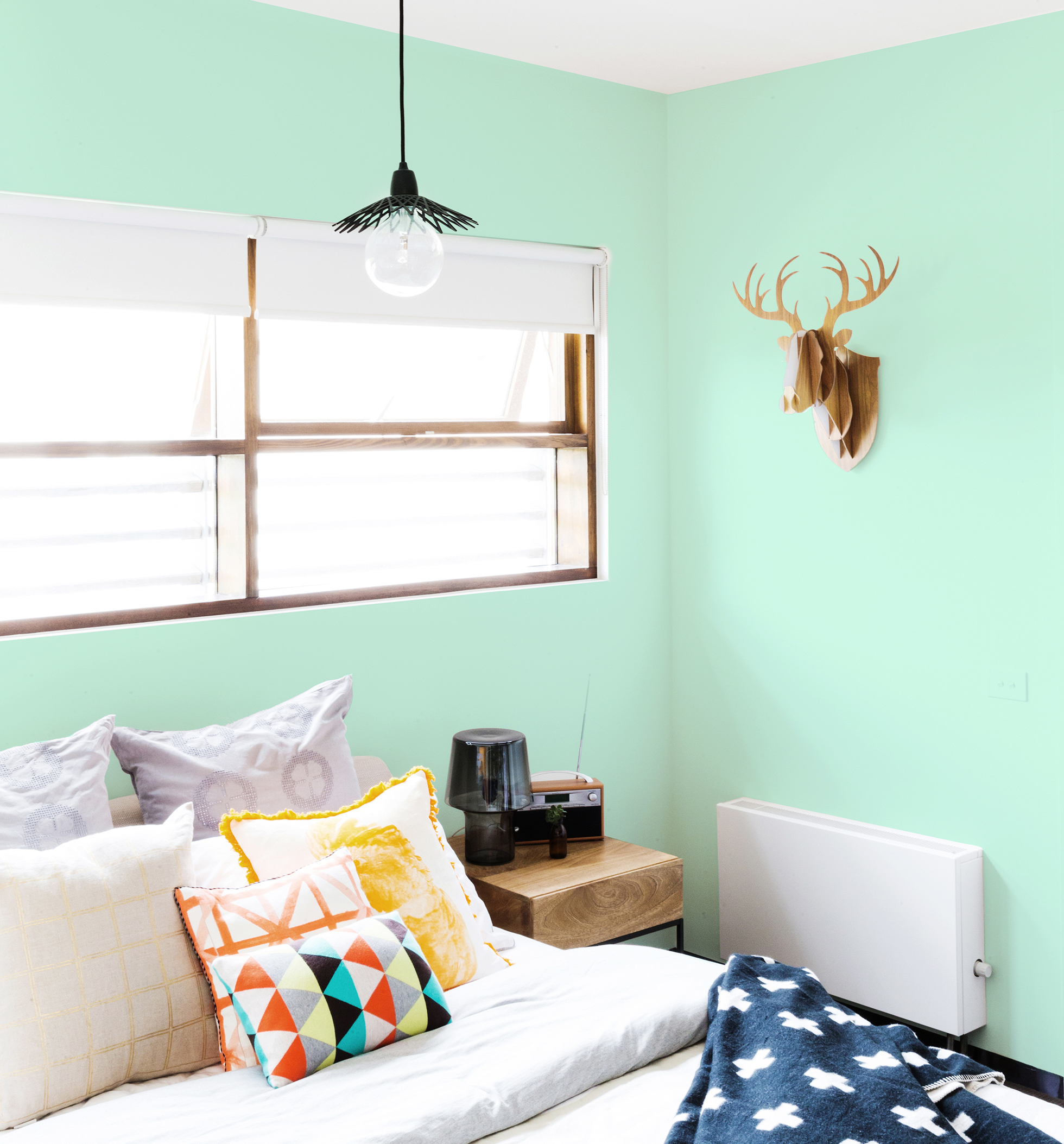 Green bedroom with large window and cardboard deer head