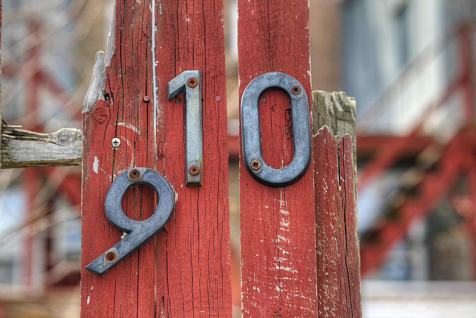 Beat up red fence with steel house numbers falling off