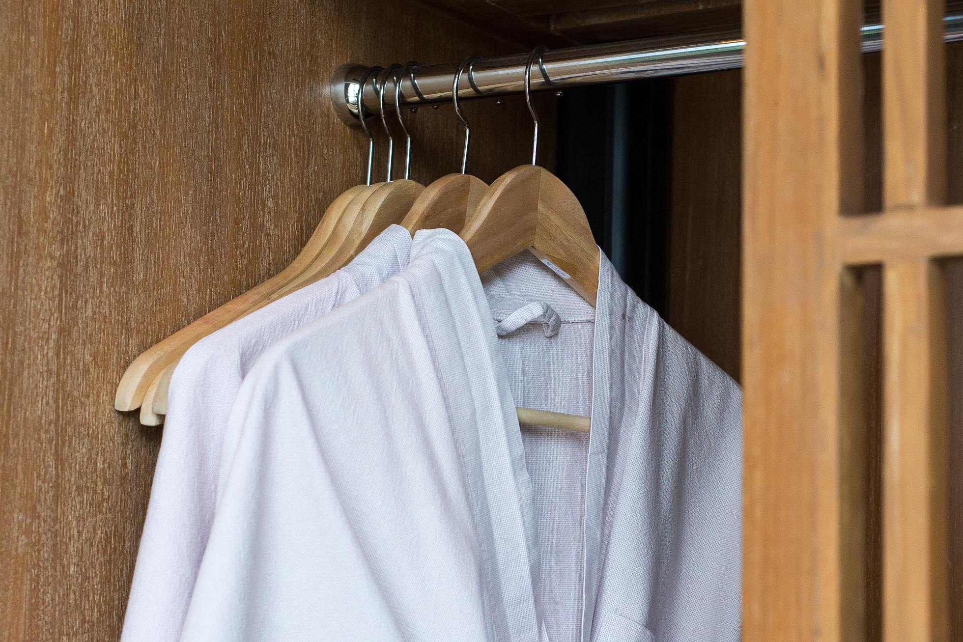 White cotton robes on hangers in a wood closet