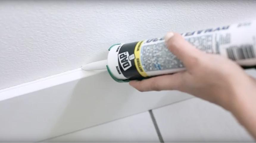 Woman applying caulk to a wall