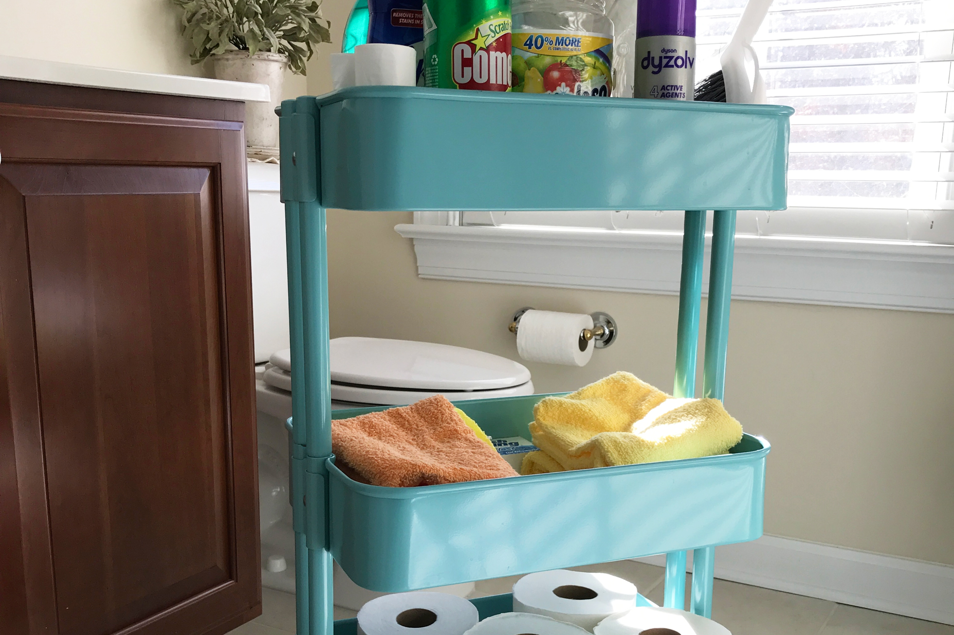 Blue cart with cleaning supplies in a bathroom