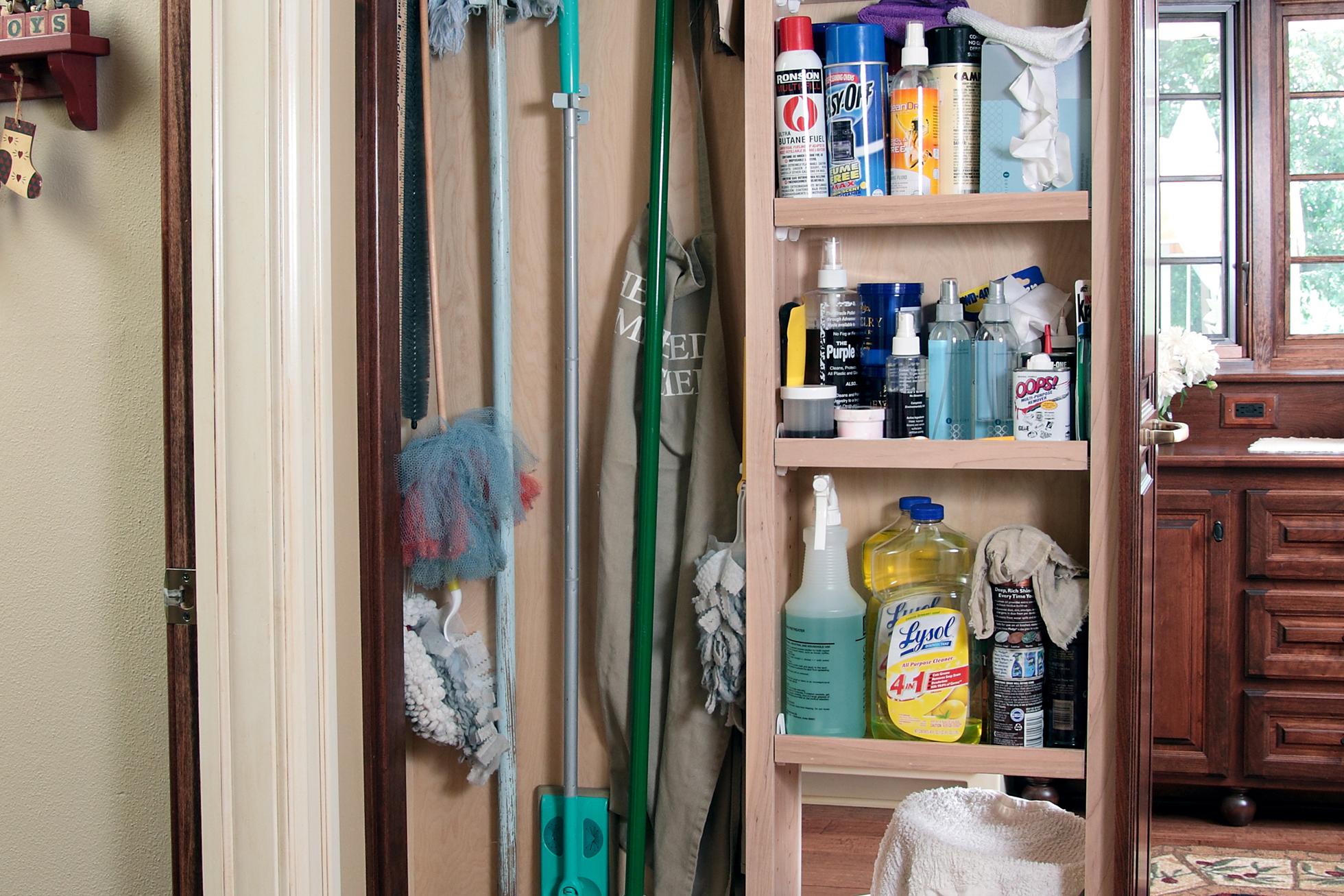A pull-out cabinet filled with cleaning supplies in kitchen
