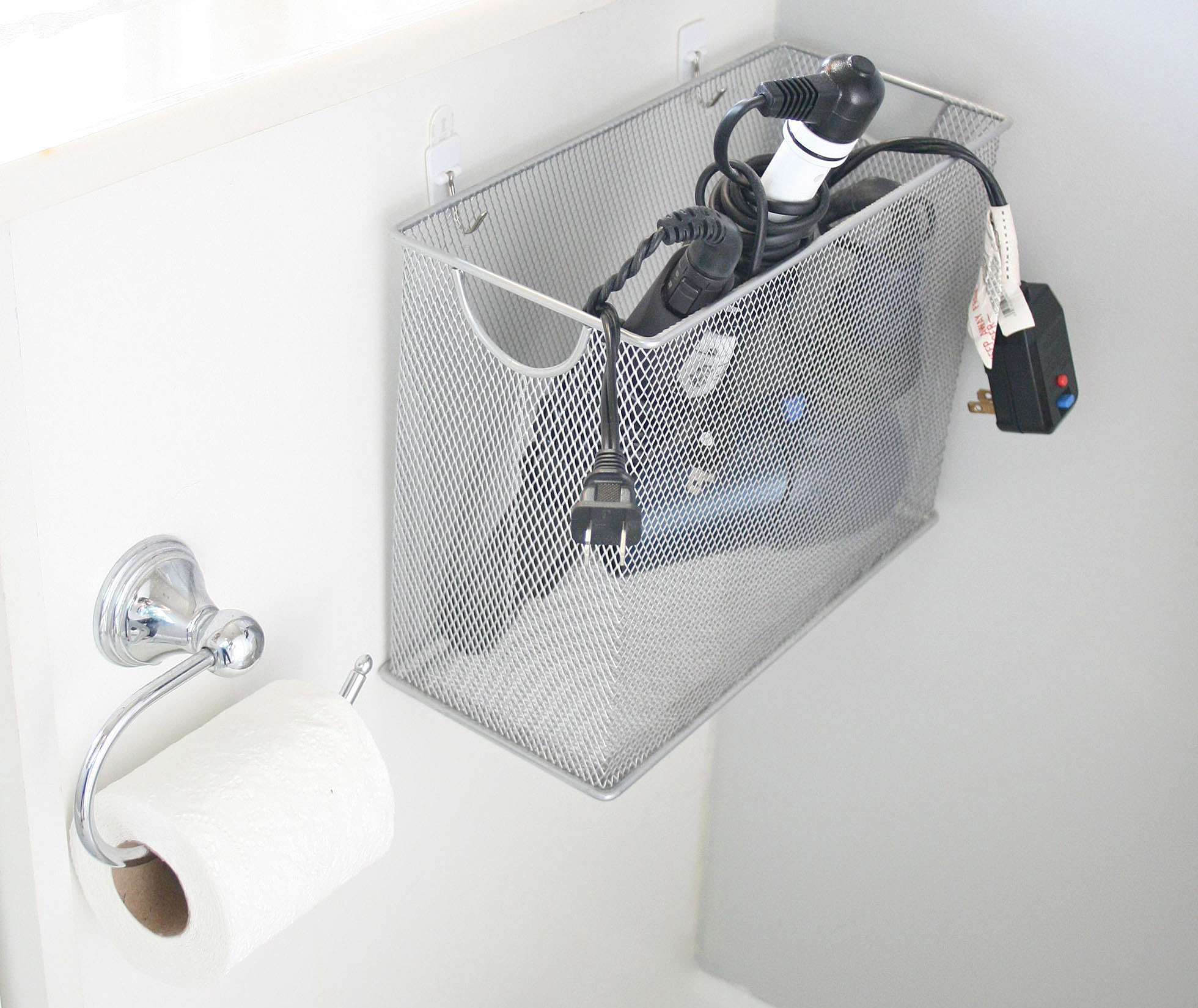 A wire basket attached to a white cabinet in a bathroom