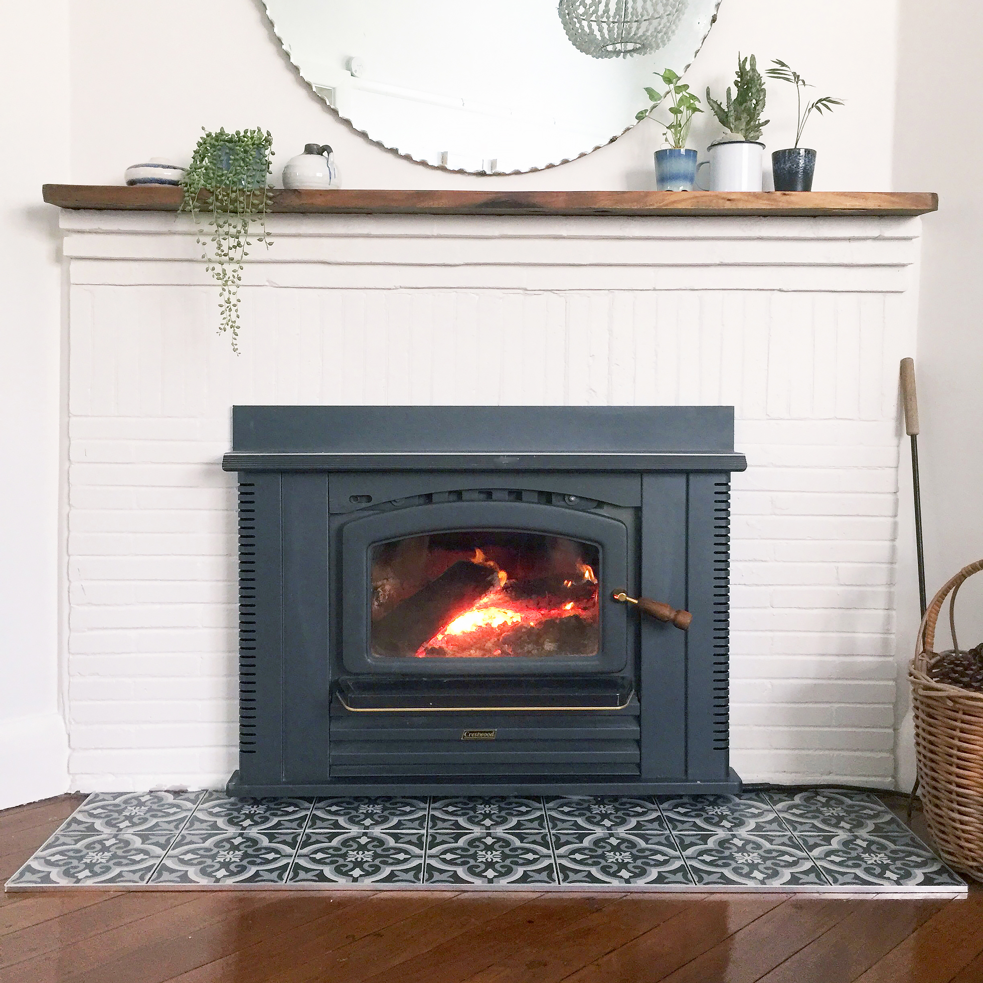 A beige-painted brick fireplace with black slate tiles