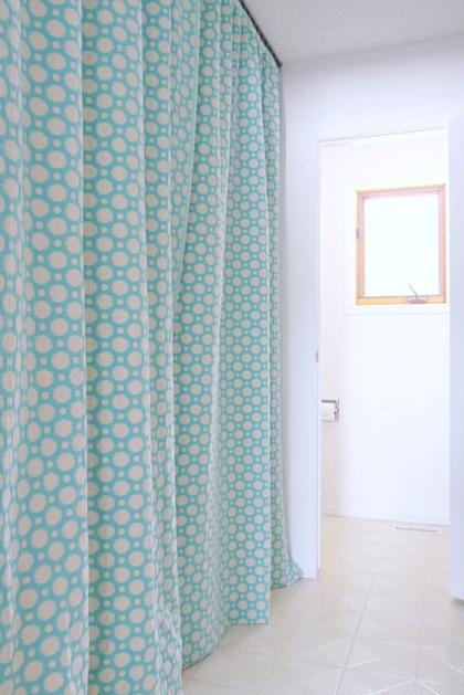 A blue green curtain hiding washer and dryer
