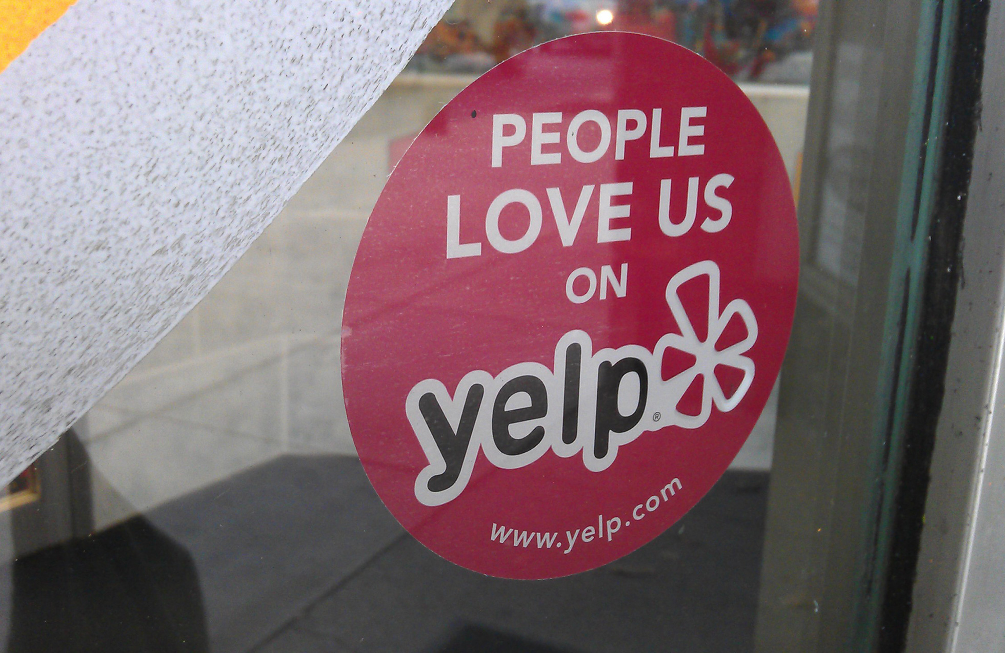 Yelp sticker on a store window