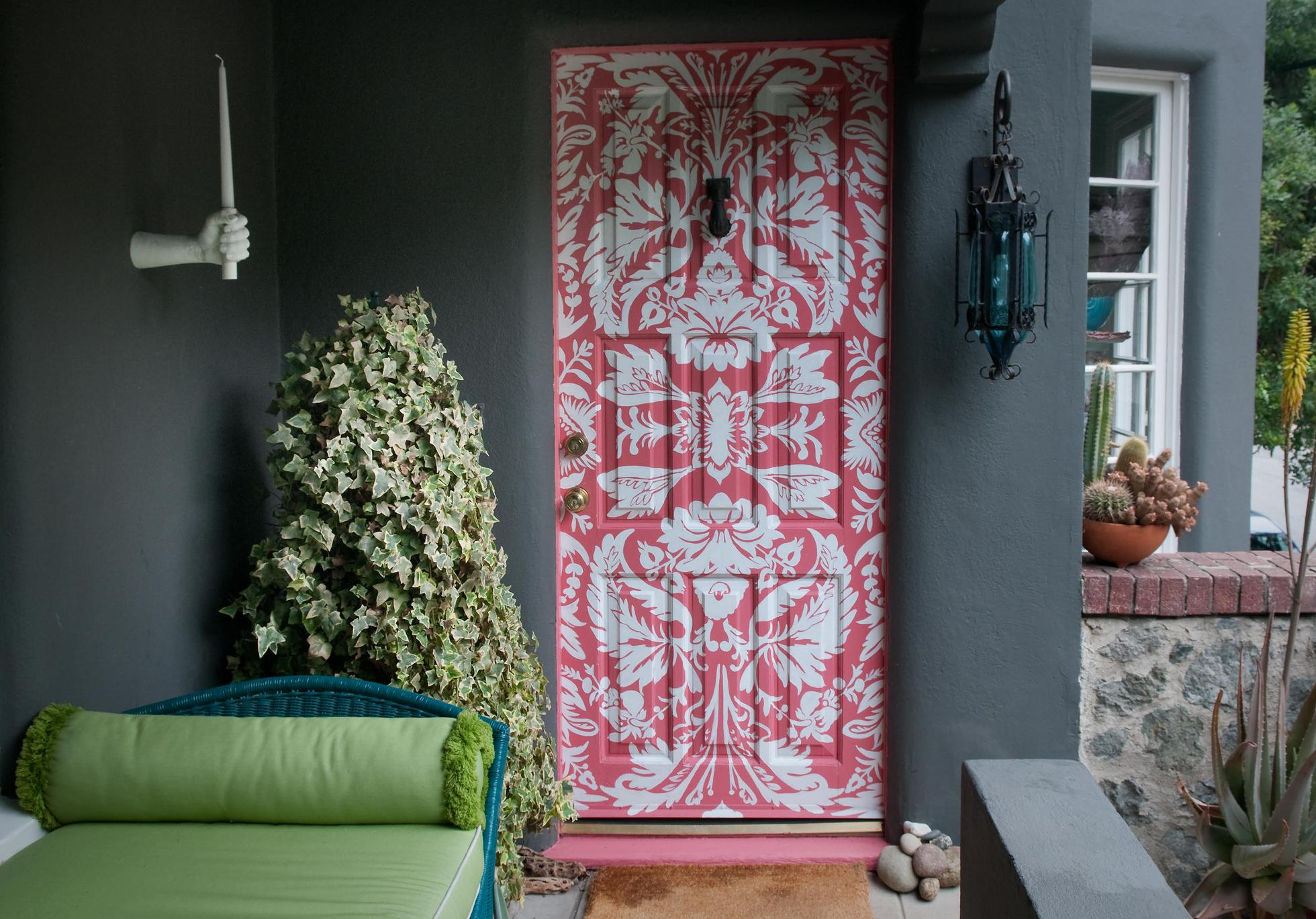 A gray stucco home with a pink and white stencil front door
