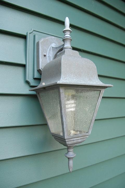 Green house siding with old silver porch light