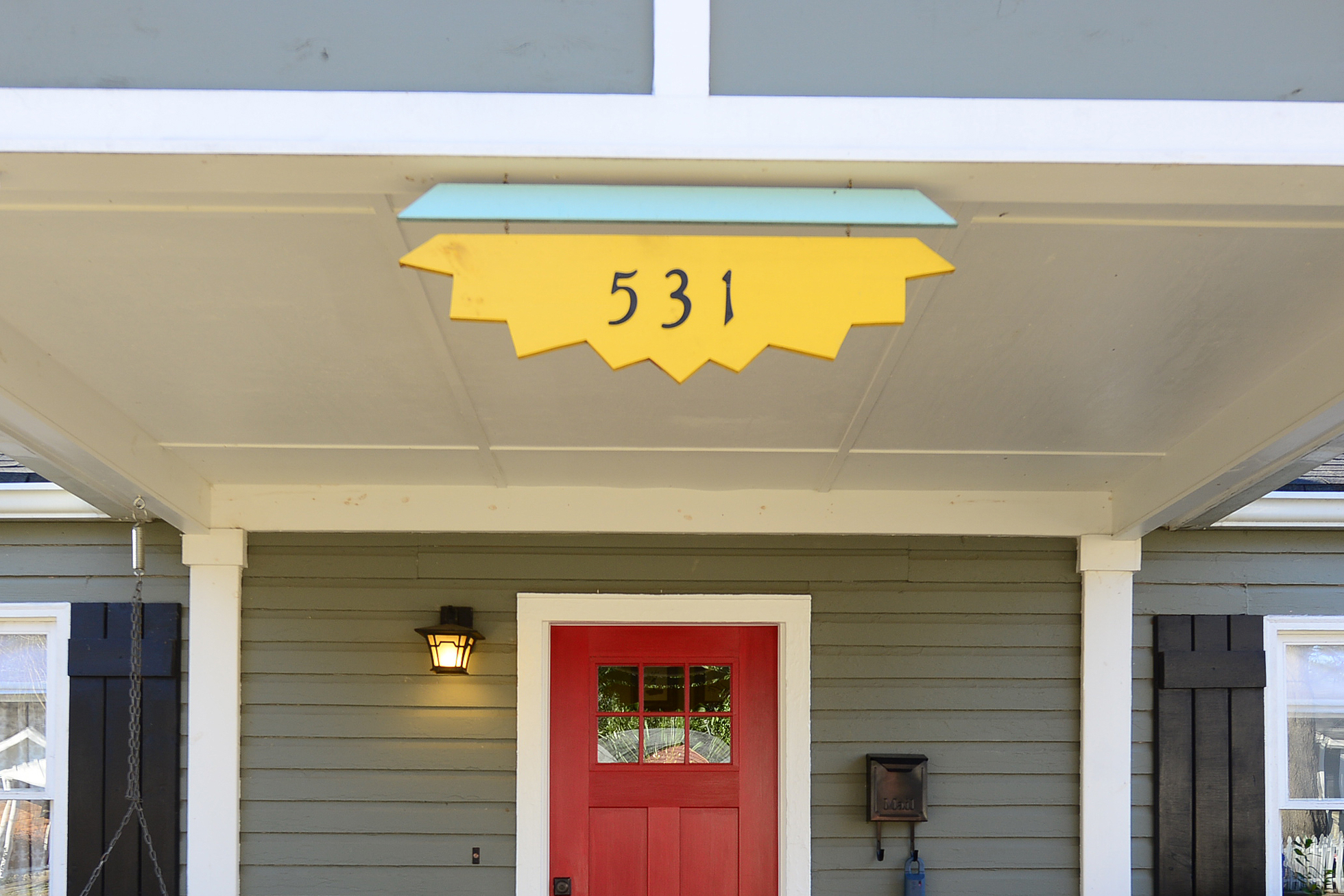 Black house numbers on a piece of yellow painted wood