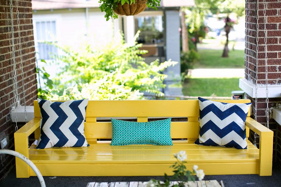 Bright yellow porch swing on a brick front porch