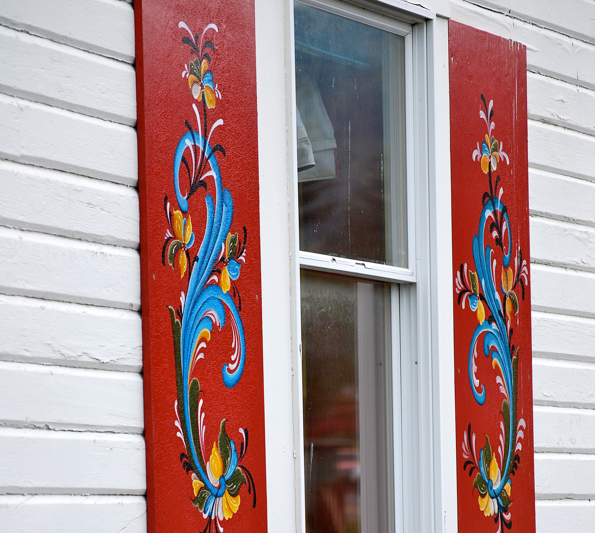 A white house with red painted shutters with rosemaling