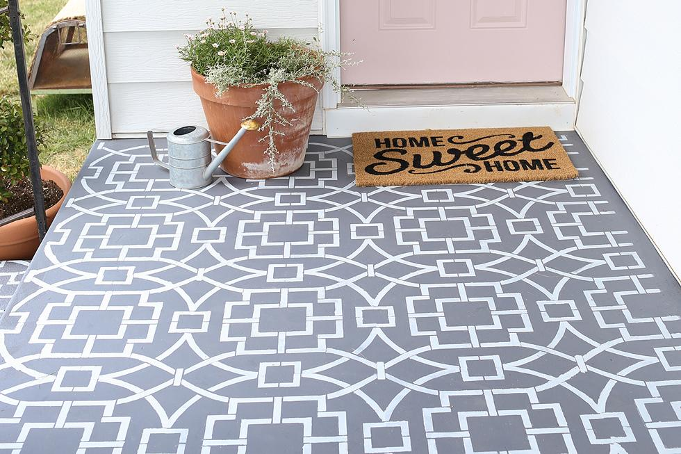 Gray and white stenciled front porch with welcome mat