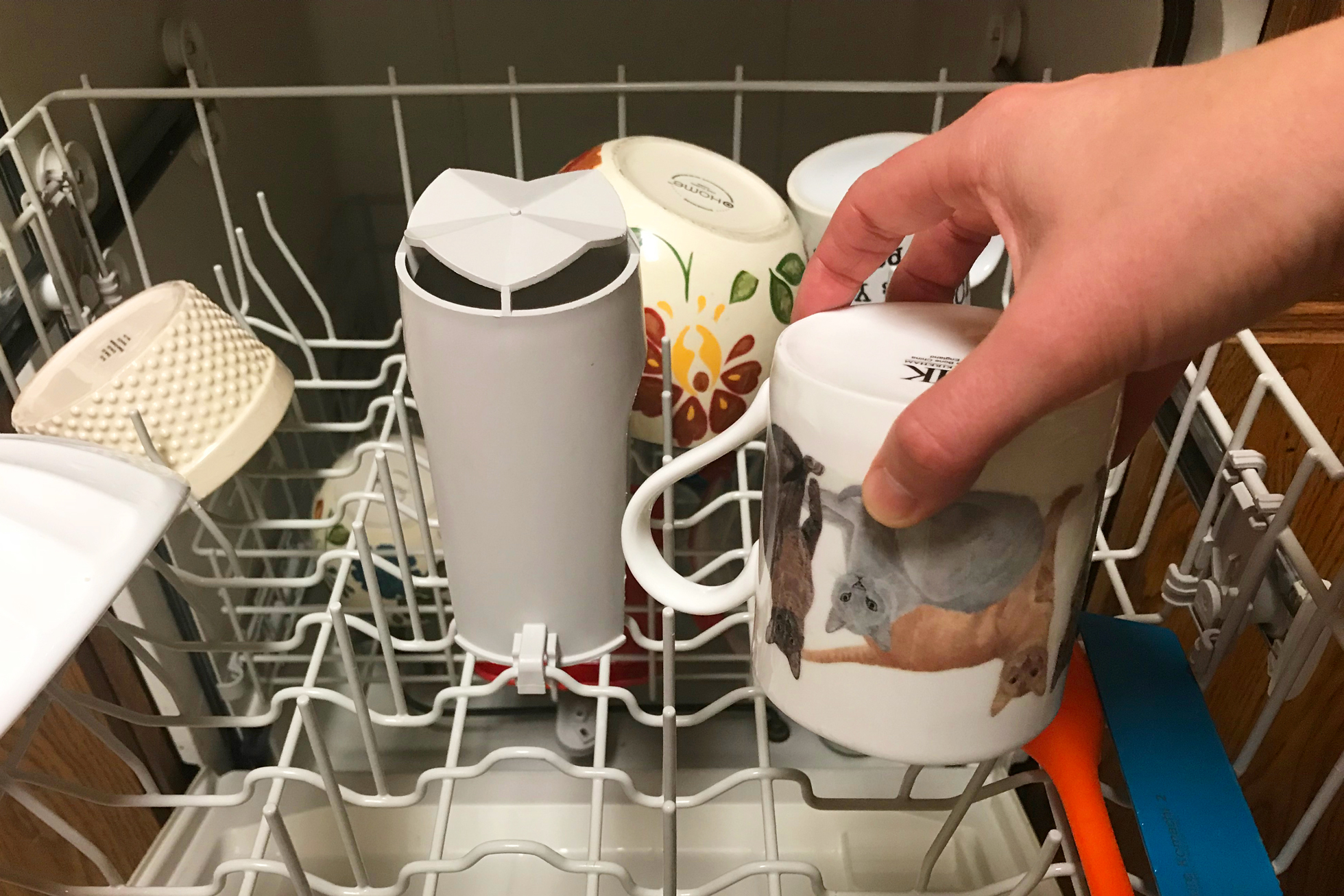 A hand putting a cat mug in a dishwasher