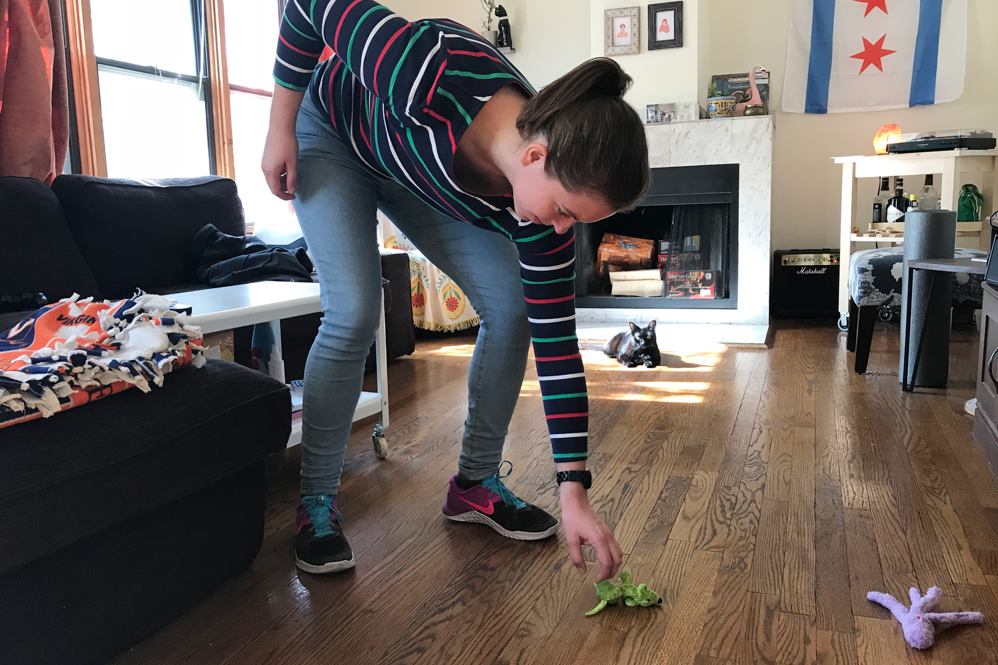 A woman picking up a green cat toy off the wood floor
