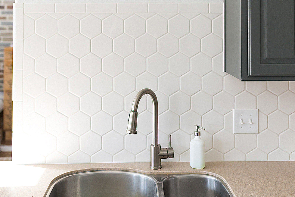 White tile backsplash above a kitchen sink
