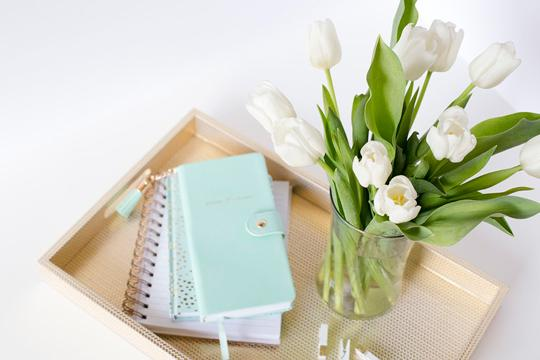 Mint notebooks on a gold tray with a vase of white tulips